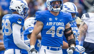 FILE - In this Oct. 6, 2018, file photo, Air Force linebacker Kyle Johnson (40), center, celebrates after a play against Navy in Colorado Springs, Colo. Air Force linebacker Kyle Johnson spent the summer interning at a think tank in Washington, D.C., that provides data-driven analysis on global conflict. He can't get too specific. The information is sensitive and classified. He can certainly reveal his game plan: To lead the Falcons back to a bowl game, attend graduate school, special operations training and one day be a leader in the intelligence community. (Dougal Brownlie/The Gazette via AP)