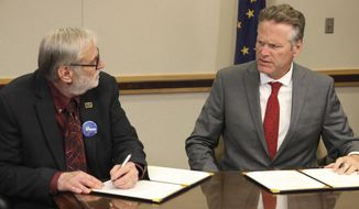University of Alaska Board of Regents chairman John Davies, left, and Gov. Mike Dunleavy sign an agreement, Tuesday, Aug. 13, 2019, in Anchorage, Alaska, that will spread $70 million in cuts to the university system over three years. That is a sharp reversal from the $135 million cut Dunleavy earlier proposed for this year. (AP Photo/Mark Thiessen)
