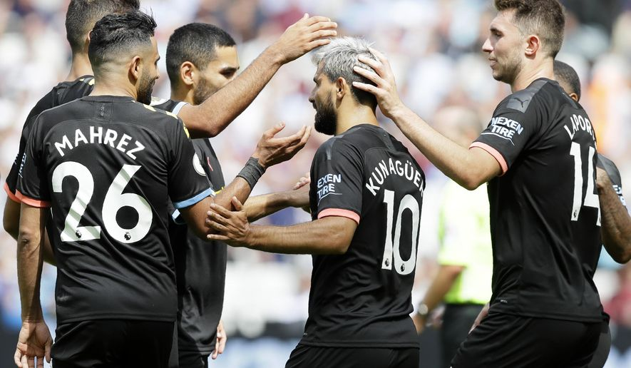 Manchester City's Sergio Aguero, center, celebrates after scoring his side's fourth goal from the penalty spot during the English Premier League soccer match between West Ham United and Manchester City at London stadium in London, Saturday, Aug. 10, 2019. (AP Photo/Kirsty Wigglesworth)