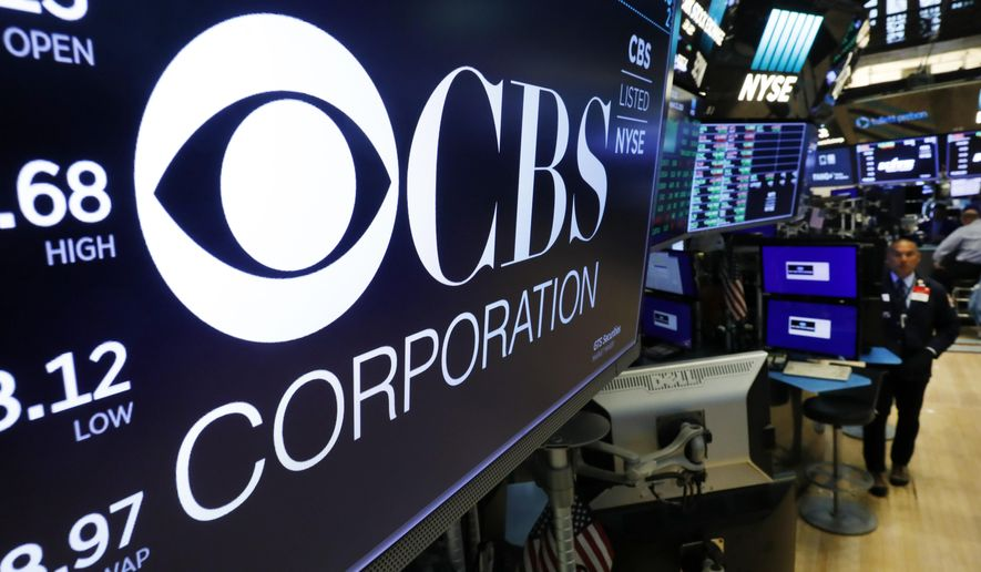 The logo for the CBS Corporation appears above a trading post on the floor of the New York Stock Exchange, Tuesday, Aug. 13, 2019. CBS and Viacom said Tuesday they will reunite, bringing together their networks and the Paramount movie studio as traditional media giants bulk up to challenge streaming companies like Netflix. (AP Photo/Richard Drew)
