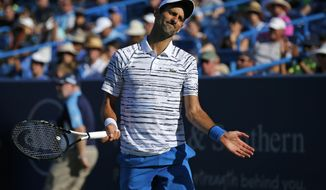 Novak Djokovic, of Serbia, reacts after giving up a point to Sam Querrey, of the United States, at the Western & Southern Open tennis tournament in Mason, Ohio, Tuesday, Aug. 13, 2019. (Sam Greene/The Cincinnati Enquirer via AP)