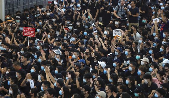 Protesters gesture as they stage a sit-in rally at the Airport in Hong Kong, Tuesday, Aug. 13, 2019. Protesters severely crippled operations at Hong Kong's international airport for a second day Tuesday, forcing authorities to cancel all remaining flights out of the city after demonstrators took over the terminals as part of their push for democratic reforms. (AP Photo/Kin Cheung)