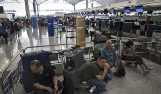 Travelers wait at the check-in counters in the departure hall of the Hong Kong International Airport in Hong Kong, Tuesday, Aug. 13, 2019. Protesters clogged the departure area at Hong Kong's reopened airport Tuesday, a day after they forced one of the world's busiest transport hubs to shut down entirely amid their calls for an independent inquiry into alleged police abuse. (AP Photo/Vincent Thian)
