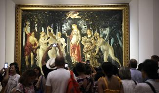 """Visitors closely admire early Renaissance painter Sandro Botticelli's """"Spring"""", at the Uffizi Gallery museum, in Florence, Italy, Tuesday, Aug. 6, 2019. To protect the masterpieces in the Uffizi Gallery's collection, the Florence museum's director climbed a ladder and hurled an employee's bicycle down at a sheet of glass specially made to keep prized pieces such as Botticelli's """"Spring"""" and """"Birth of Venus"""" safe from vandals. (AP Photo/Luca Bruno)"""