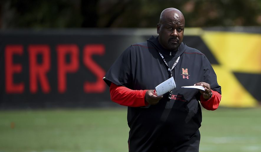 In this Aug. 2, 2019, file photo, Maryland head coach Mike Locksley looks on as his team works out during a NCAA college football training camp in College Park, Md. Coming off the darkest season in the history of the Maryland football program, the Terrapins are poised to enter a new era under Mike Locksley, hired in December after a successful run as Alabama's offensive coordinator, who remembers what it was like when the team competed for conference titles and counted on playing in bowl games. (AP Photo/Will Newton, File) **FILE**