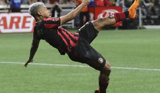 Atlanta United forward Josef Martinez attempts a bicycle shot on goal that he missed against New York City FC in their soccer match on Sunday, August 11, 2019, in Atlanta. Martinez went on to score both his team's goals in a 2-1 victory over NYCFC. (Curtis Compton/Atlanta Journal-Constitution via AP)