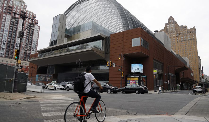 A cyclist passes by The Kimmel Center for the Performance Arts, Tuesday, Aug. 13, 2019, in Philadelphia. The Philadelphia Orchestra has canceled upcoming performances there due to coronavirus concerns, but said on March 12, 2020, that that evening's performances will be streamed for free online. (AP Photo/Matt Slocum) **FILE**