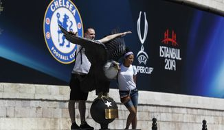 Tourists pose for photos outside Besiktas Park in Istanbul, Sunday, Aug.11, 2019, where the UEFA Super Cup soccer match between Liverpool and Chelsea will be played on Wednesday, Aug. 14. (AP Photo/Lefteris Pitarakis)