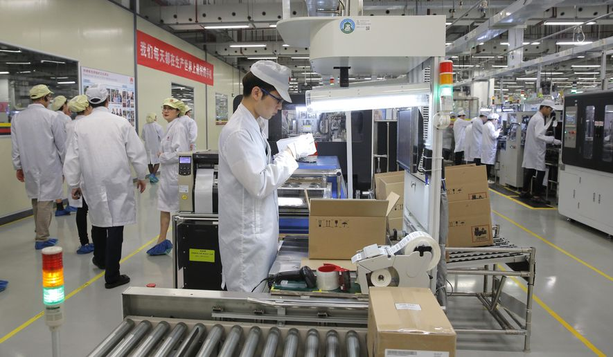 FILE - In this March 6, 2019, file photo a staff member works on a mobile phone production line during a media tour in Huawei factory in Dongguan, China's Guangdong province. Huawei Technologies Co. is one of the world's biggest supplier of telecommunications equipment. The United States is delaying tariffs on Chinese-made cellphones, laptop computers and other items and removing other Chinese imports from its target list altogether in a move that triggered a rally on Wall Street. (AP Photo/Kin Cheung, File)