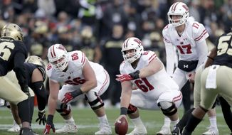 FILE - In this Nov. 17, 2018, file photo, Wisconsin's Tyler Biadasz (61) gestures as he prepares to snap the ball to quarterback Jack Coan during the first half against Purdue in an NCAA college football game in West Lafayette, Ind. Returning starting center  Biadasz, who underwent hip surgery during the offseason, will anchor the line after earning first-team All-Big Ten honors in 2018. (AP Photo/Michael Conroy, File)