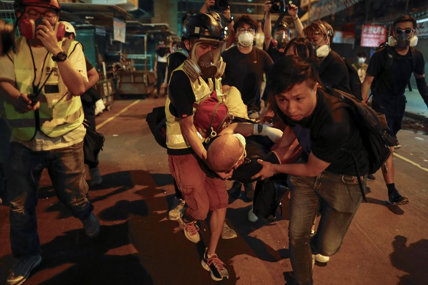 Medical staff and protesters carry an injured man as they face off with police near the Shum Shui Po police station in Hong Kong on Wednesday. Police fired tear gas at the protesters. Meanwhile, five people were arrested over violence at the airport. (Associated Press)