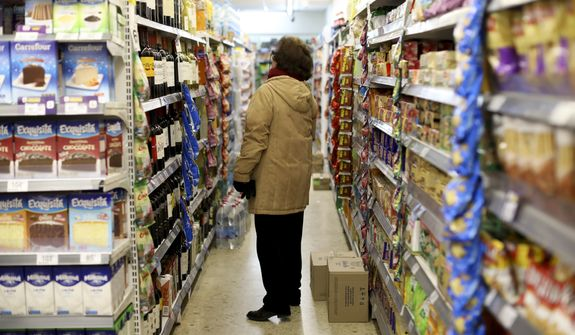 "A woman checks prices at a supermarket in Buenos Aires, Argentina, Wednesday, Aug. 14, 2019. President Mauricio Macri announced economic relief for poor and working-class Argentines that include an increased minimum wage, reduced payroll taxes, a bonus for informal workers and a freeze in gasoline prices. The conservative leader said Wednesday he's acting in recognition of the ""anger"" Argentines expressed in Sunday's primary election, when Macri trailed his populist rival by 15 percentage points. (AP Photo/Natacha Pisarenko)"
