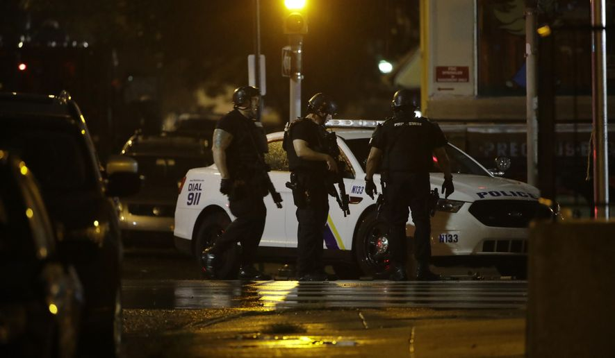 Authorities continue their investigation of a shooting where multiple police officers were shot, Wednesday, Aug. 14, 2019, in Philadelphia. (AP Photo/Matt Rourke)