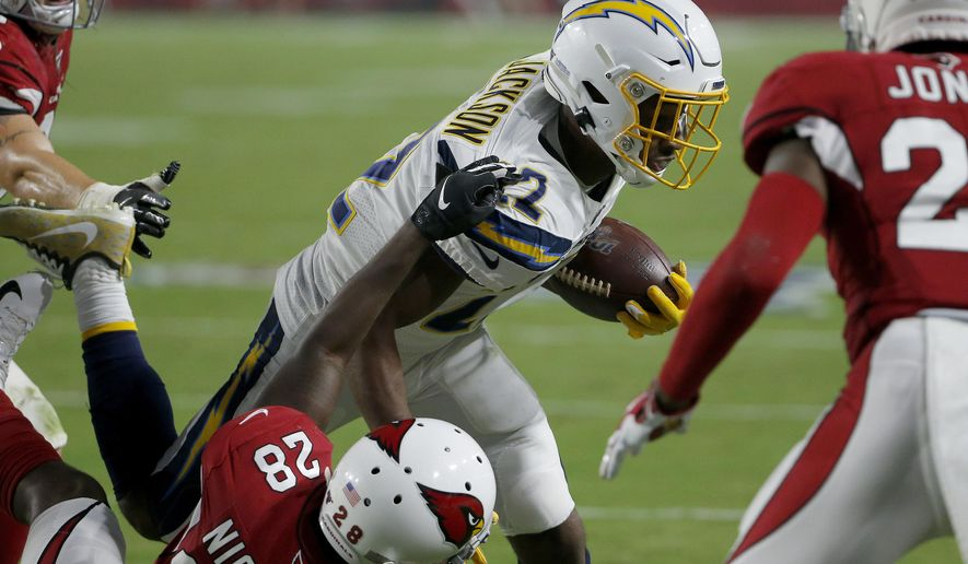 Los Angeles Chargers running back Justin Jackson (22) runs in for a touchdown as Arizona Cardinals cornerback Deatrick Nichols (28) defends during the first half of an NFL preseason football game, Thursday, Aug. 8, 2019, in Glendale, Ariz. (AP Photo/Rick Scuteri)