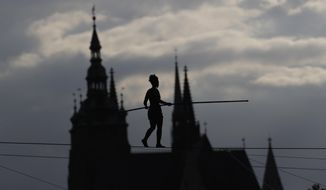 French tightrope walker Tatiana-Mosio Bongoga balances over the Vltava river during her performance to open an international new circus festival in Prague, Czech Republic, Wednesday, Aug. 14, 2019. The Prague Castle is in the background. (AP Photo/Petr David Josek)