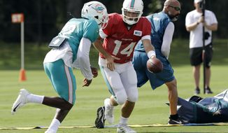 Miami Dolphins quarterback Ryan Fitzpatrick (14) hands off to running back Kenyan Drake (32) during an NFL football training camp practice with the Tampa Bay Buccaneers Tuesday, Aug. 13, 2019, in Tampa, Fla. (AP Photo/Chris O'Meara)