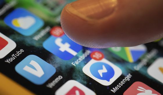 In this Sunday, Aug. 11, 2019, file photo, an iPhone displays the apps for Facebook and Messenger in New Orleans. (AP Photo/Jenny Kane) ** FILE **