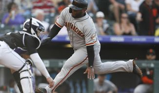 San Francisco Giants' Pablo Sandoval, right, scores on a single by Brandon Crawford as Colorado Rockies catcher Tony Wolters waits for the throw during the first inning of a baseball game Saturday, Aug. 3, 2019, in Denver. (AP Photo/David Zalubowski)