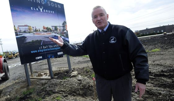"""FILE - In this May 2019 file photo, Elk Grove Village Mayor Craig Johnson walks the $1 billion Elk Grove Technology Park which was the former 85-acre Busse Farm.Johnson came up with the idea of bowl sponsorship while he was in Wisconsin a couple winters ago. Elk Grove Village had been advertising on Chicago Cubs broadcasts, but it stepped back because of pricing and was looking for something new.  Johnson was watching a bowl game on TV when it came to him. With some help from 4FRONT, a sports marketing company, Johnson and Elk Grove settled on a $300,000 deal with the ESPN-owned Bahamas Bowl. The village also considered the Hawaii Bowl and New Mexico Bowl. They used """"Makers Wanted"""" in the bowl title as part of a campaign to promote a local industrial park. (Mark Welsh/Daily Herald via AP, File)"""
