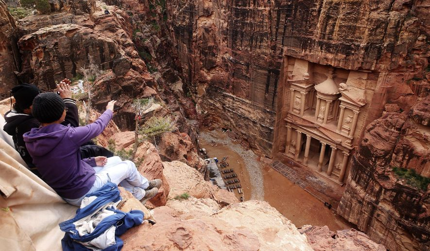 In this Feb. 13, 2017, file photo, tourists point at the Treasury, in the kingdom's Petra archaeological park, southern Jordan. (AP Photo/Sam McNeil, File)