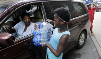 Elaine Younger, 11, and Tahvion Williams, 14, right, load water in their family's van at the Newark Health Department in Newark, N.J., Wednesday, Aug. 14, 2019. Residents began picking up bottled water on Monday, days after elevated lead levels were found in homes where city-issued filters had been distributed months ago as part of an ongoing effort to combat contamination. (AP Photo/Seth Wenig)