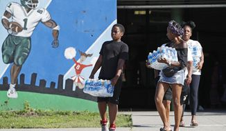 Rahjiah McBride, of Chester, Pa., center, helps her relatives who are Newark residents pick up cases of water from the Boylan Street Recreation Center, Monday, Aug. 12, 2019, in Newark, N.J., after New Jersey's governor and Newark's mayor vowed to provide bottled water to city residents with lead service lines. Environmental Protection Agency tests indicated that filters distributed earlier might not be protecting residents against elevated lead levels in some areas. (AP Photo/Kathy Willens)