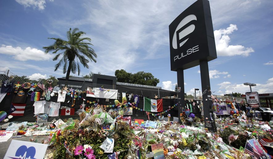In this July 11, 2016, file photo, a makeshift memorial continues to grow outside the Pulse nightclub in Orlando, the day before the one month anniversary of a mass shooting, in Orlando, Fla. A group of survivors and family members of those killed have formed an organization to oppose the building of a private museum to honor the victims of a mass shooting at the Florida nightclub three years ago. Members of the Community Coalition Against a Pulse Museum say the nightclub should be torn down and the nightclub's owner shouldn't build a private museum. (AP Photo/John Raoux, File)