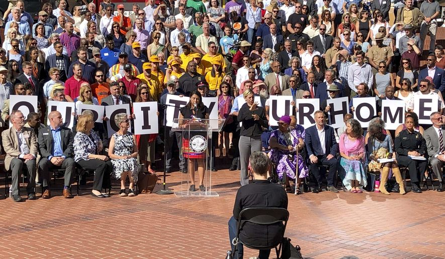 """Members of dozens of civic leaders hold up signs spelling out Our City Our Home on Wednesday, Aug. 14, 2019, in Portland, Ore., during a rally to support the city in advance of protests planned for Saturday. The Mayor of Portland, Ted Wheeler, said anyone planning violence or espousing hatred at an upcoming weekend protest by right-wing groups in the liberal city """"are not welcome here."""" Wheeler spoke with other city leaders ahead of the event Saturday, which is also expected to bring out anti-fascist protesters. Anticipating trouble, none of the city's nearly 1,000 police officers will have the day off Saturday. (AP Photo/Gillian Flaccus)"""