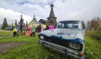 In this photo taken on Oct. 7, 2018, people walk the street with the 18th century Trinity Church in the background in the village of Nyonoksa, northwestern Russia. The Aug. 8, 2019, explosion of a rocket engine at the Russian navy's testing range just outside Nyonoksa led to a brief spike in radiation levels and raised new questions about prospective Russian weapons. (AP Photo/Sergei Yakovlev)