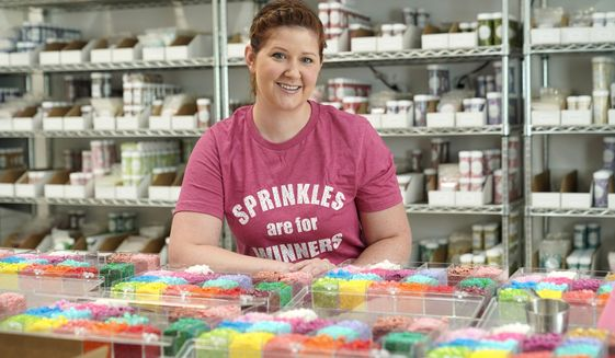 In this Tuesday, Aug. 13, 2019, photo Elizabeth Butts, owner of Sprinkle Pop, a company based in Houston that makes upscale sprinkles for bakers, poses for a photo inside her business in Houston. Butts is building out and equipping a 10,000 foot facility for storage and shipping. She's reinvesting the company's profits rather than seeking investors, which will make it easier for her to run the company, but she also doesn't want to burden her company with debt. (AP Photo/David J. Phillip)