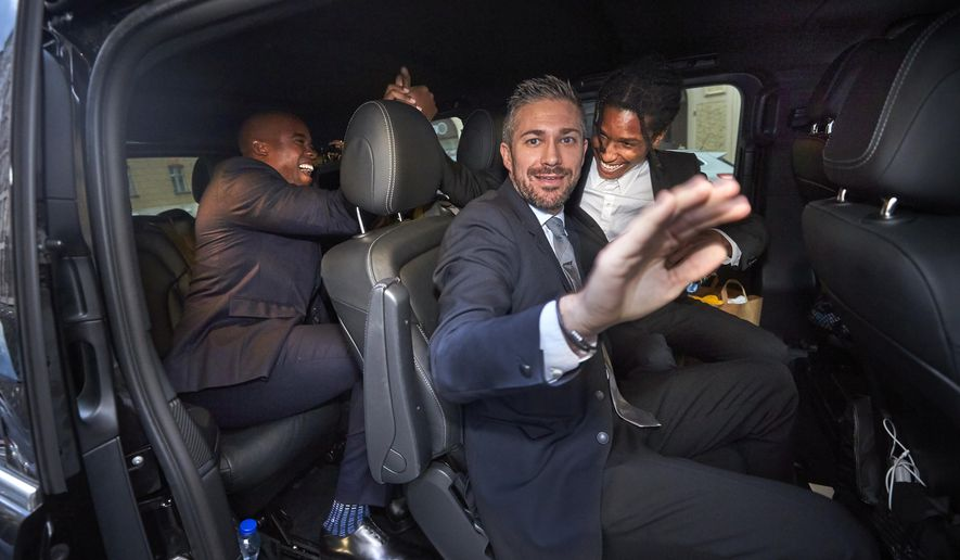 A$AP Rocky, background right, leaves the district court in Stockholm by car, after the third day of his trial, Friday, Aug. 2, 2019. He and two other American suspects were temporarily freed from a Swedish jail to head back to the U.S., as judges mull a verdict in the assault case against them. (Fredrik Persson/TT via AP)