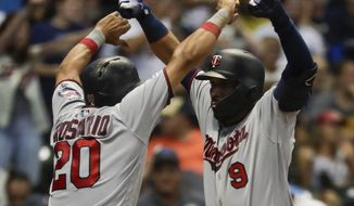 Minnesota Twins' Marwin Gonzalez celebrates with Eddie Rosario after hitting a three-run home run during the eighth inning of a baseball game against the Milwaukee Brewers Tuesday, Aug. 13, 2019, in Milwaukee. (AP Photo/Morry Gash)
