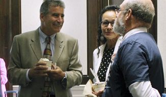 New University of Connecticut president Thomas Katsouleas, left, speaks with board of trustees member Andrea Dennis-LaVigne, center, and Steven Zinn, right, head of the Department of Animal Sciences, outside the board of trustees meeting on Wednesday, Aug. 14, 2019, in Storrs, Conn. Katsouleas has begun implementing a plan he said will help UConn double its research spending in the next decade. (AP Photo/Pat Eaton-Robb)