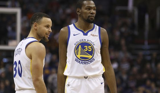 FILE - In this Feb. 8, 2019, file photo, Golden State Warriors guard Stephen Curry (30) and forward Kevin Durant (35) pause during the first half of an NBA basketball game against the Phoenix Suns Friday, Feb. 8, 2019, in Phoenix. Someday, years or even decades from now, at one of those celebratory reunions teams like to do, Stephen Curry knows he and Kevin Durant will reminisce with fondness about their three insanely successful years together on the Golden State Warriors. They will reflect on the greatness, the fun, all they learned from each other shooting side by side day after day to become better from their time as teammates. Two championships, a pair of NBA Finals MVP awards for Durant. (AP Photo/Ross D. Franklin, File)