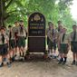 Boy Scout Troop 4077 of Alexandria, Virginia, stand around the newly dedicated sign at Douglass Memorial Cemetery on Thursday. The sign was part of an Eagle Scout project for Griffin Burchard, 16, who is standing to the right of the sign in this photo. (Sophie Kaplan/ The Washington Times)