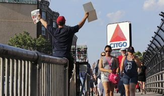 In this Wednesday, June 1, 2016, file photo, a hawker sells programs, with the iconic Citgo sign in the background, as fans walk from Kenmore Square to a baseball game at Fenway Park in Boston. The Boston Landmarks Commission meets Tuesday to decide whether to launch a study to determine if the sign qualifies for preservation as a historic landmark. Thousands of Bostonians have signed a petition clamoring to save it. (AP Photo/Charles Krupa) ** FILE **