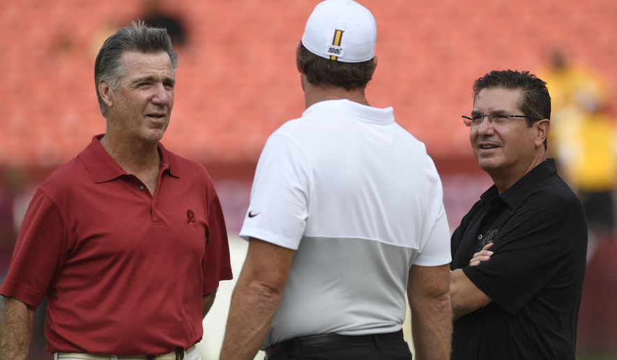 Washington Redskins team owner Dan Snyder, right, and Washington Redskins team president Bruce Allen, left, talk with head coach Jay Gruden, center, before the start of a NFL preseason football game against the Cincinnati Bengals in Landover, Md., Thursday, Aug. 15, 2019. (AP Photo/Susan Walsh)