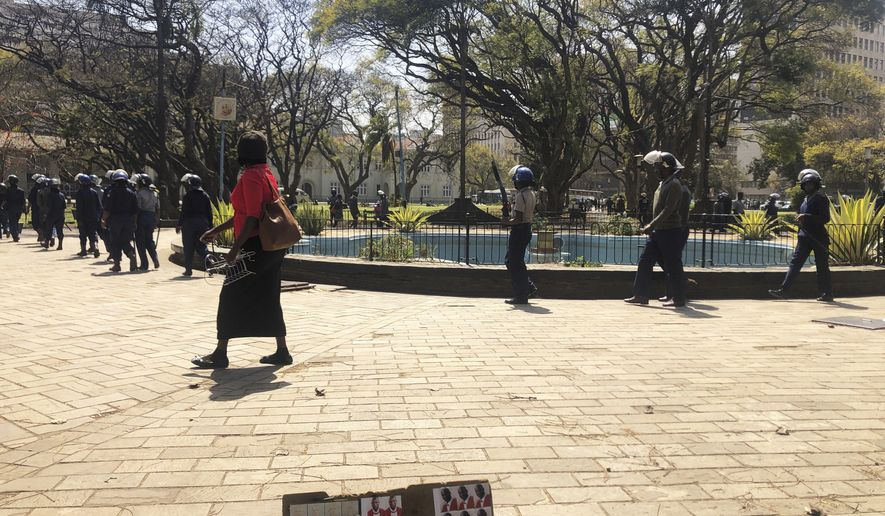 """Armed riot police patrol the streets in Harare, Thursday, Aug, 15, 2019. In a show of force to discourage anti government protests, Zimbabwe police with water cannons patrolled the capital's streets and warned residents, """"you will rot in jail"""" if they participated in the demonstrations planned for Friday. (AP Photo/Tsvangirayi Mukwazhi)"""