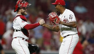 Cincinnati Reds catcher Tucker Barnhart, left, and relief pitcher Raisel Iglesias celebrate the team's 2-1 win over the St. Louis Cardinals in a baseball game Thursday, Aug. 15, 2019, in Cincinnati. (AP Photo/Gary Landers)