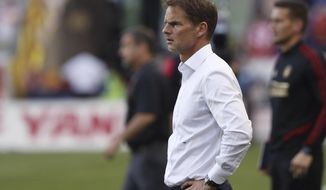 """FILE - In this May 19, 2019, file photo, Atlanta United coach Frank de Boer watches during the second half of the team's MLS soccer match against the New York Red Bulls in Harrison, N.J. De Boer said he regrets his choice of words in a British newspaper interview about gender equity in soccer and stressed that he's a big supporter of the women's game. De Boer faced backlash before Wednesday's Campeones Cup game for his comments in an article published by The Guardian, in which he said it was """"ridiculous"""" that female players expect to receive the same World Cup pay as the men. (AP Photo/Steve Luciano, File)"""