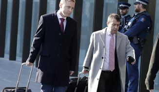 Defense lawyers for Brenton Tarrant, Jonathon Hudson, left, and Shane Tait arrive at the Christchurch District Court in Christchurch, New Zealand, Thursday, Aug. 15, 2019. The trial of the man accused of killing 51 people at two Christchurch mosques could be delayed by several weeks next year to avoid beginning during the Islamic holy month of Ramadan. (AP Photo/Mark Baker)