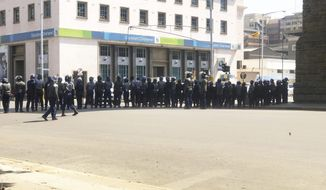 """Armed Riot Police block a main road during a patrol on the streets in Harare, Thursday, Aug, 15, 2019.  In a show of force to discourage anti government protests, Zimbabwe police with water cannons patrolled the capital's streets and warned residents, """"you will rot in jail"""" if they participated in the demonstrations planned for Friday. (AP Photo/Tsvangirayi Mukwazhi)"""