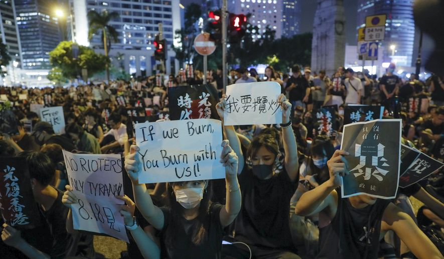 Pro-democracy protesters display placards during a rally organized by higher education students in Chater Garden in Hong Kong Friday, Aug. 16, 2019.  China's paramilitary People's Armed Police marched and practiced crowd control tactics at a sports complex in Shenzhen across the border in Hong Kong on Friday, in what some have interpreted as a threat against pro-democracy protesters. (AP Photo/Kin Cheung)