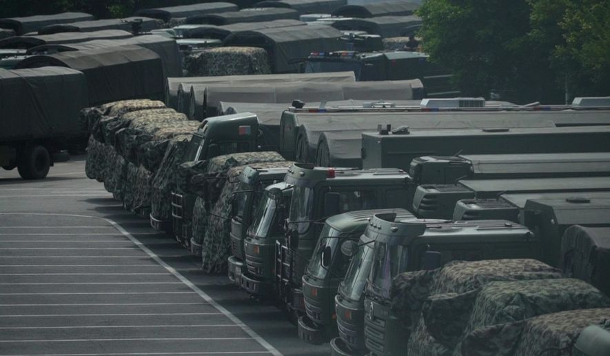 In this image made from video, armed police vehicles are parked outside Shenzhen Bay Stadium in Shenzhen, near Hong Kong, Friday, Aug. 16, 2019. Satellite photos show what appear to be armored personnel carriers and other vehicles belonging to the China's paramilitary People's Armed Police parked in a sports complex in the city of Shenzhen, in what some have interpreted as a threat from Beijing to use increased force against pro-democracy protesters across the border in Hong Kong.(AP Photo/Dake Kang)