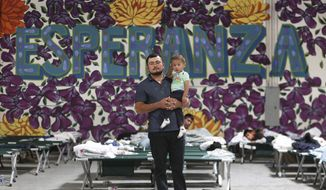 FILE - In this Wednesday, April 24, 2019 file photo, a Guatemalan man poses for a photo with his young son at the new Casa del Refugiado in east El Paso, Texas. Behind him is a full-wall mural which reads Esperanza, or hope. A federal appeals court ruling will allow the Trump administration to begin rejecting asylum at some parts of the U.S.- Mexico border for migrants who arrived after transiting through a third country. (Mark Lambie/The El Paso Times via AP, File)