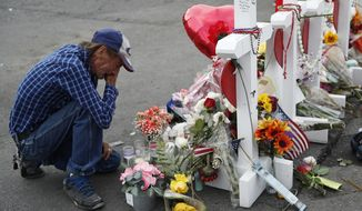 In this Aug. 6, 2019 file photo, Antonio Basco cries beside a cross at a makeshift memorial near the scene of a mass shooting at a shopping complex, in El Paso, Texas. Basco, whose 63-year-old wife was among the Texas mass shooting victims says he has no other family and welcomes anyone wanting to attend her services in El Paso. Margie Reckard was among 22 people fatally shot on Aug. 3 at a Walmart. Reckard and Basco were married 22 years. (AP Photo/John Locher, File)