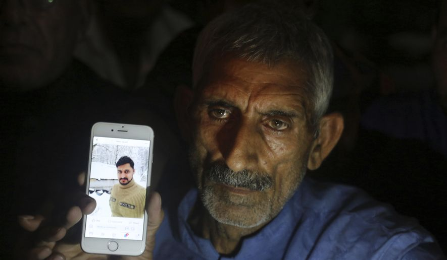 Pakistan's Mohammad Aslam shows a picture of his son Taimoor Aslam, who he said lost his life at the Kashmir border area called the Line of Control between Indian and Pakistan, Thursday, Aug. 15, 2019, in Lahore, Pakistan. (AP Photo/K.M. Chaudhry)