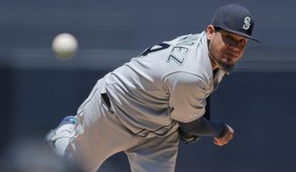 FILE - In this April 24, 2019 file photo, Seattle Mariners starting pitcher Felix Hernandez works against a San Diego Padres batter during the first inning of a baseball game, in San Diego. Venezuela was once an incubator of Major League Baseball stars such Hernandez. But chances for Venezuelans to make it to the MLB are now small and getting remoter. (AP Photo/Gregory Bull, File)