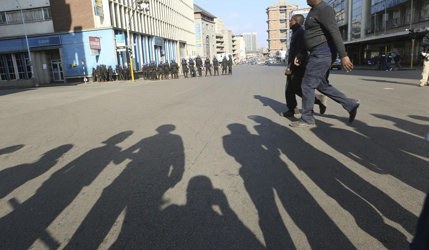 People walk past armed riot police ahead of a planned protest in Harare, Friday, Aug. 16, 2019. Zimbabwe's police patrolled the streets of the capital Friday morning while many residents stayed home fearing violence from an anti-government demonstration planned by the opposition. (AP Photo/Tsvangirayi Mukwazhi)