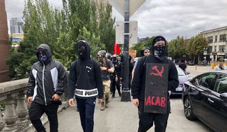 Anti-fascist (Antifa) counter-demonstrators cross the Burnside Bridge across the Willamette River from the west side of the city to the east side in search of the far-right group, the Proud Boys, in Portland, Ore., Saturday, Aug. 17, 2019. (AP Photo/Gillian Flaccus)  **FILE**